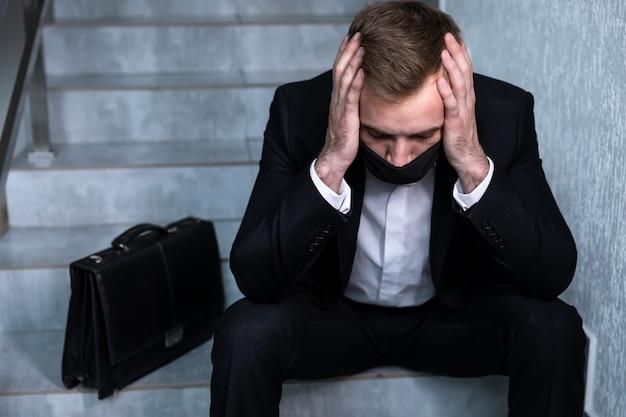 계단에 머리를 들고 사업가 코로나 바이러스 위기, 우울증 및 실업 개념으로 인해 해고되었습니다.