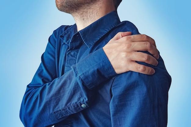 Бизнесмен, держащий руку к его ноющей спине. молодой парень в синей рубашке жалуется на боль в плече. перелом предплечья. концепция здоровья