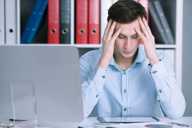 Businessman holding his head worried