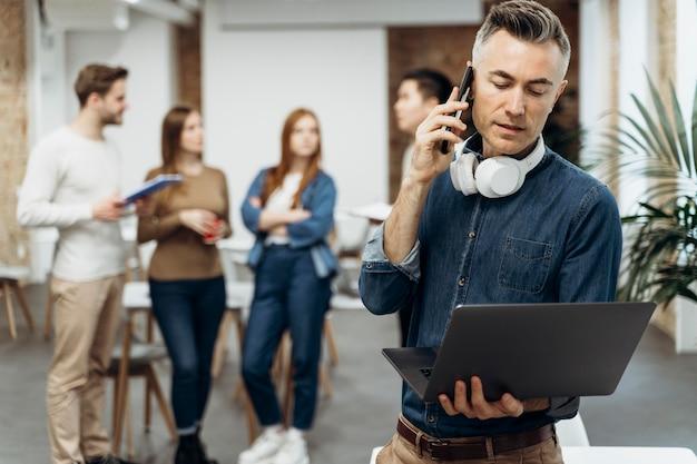 Бизнесмен, держащий свой ноутбук во время разговора по телефону