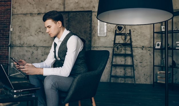 Бизнесмен держит свой телефон, сидя перед ноутбуком