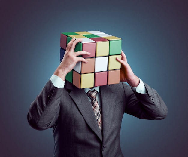 Businessman holding his rubik cube head isolated on gray