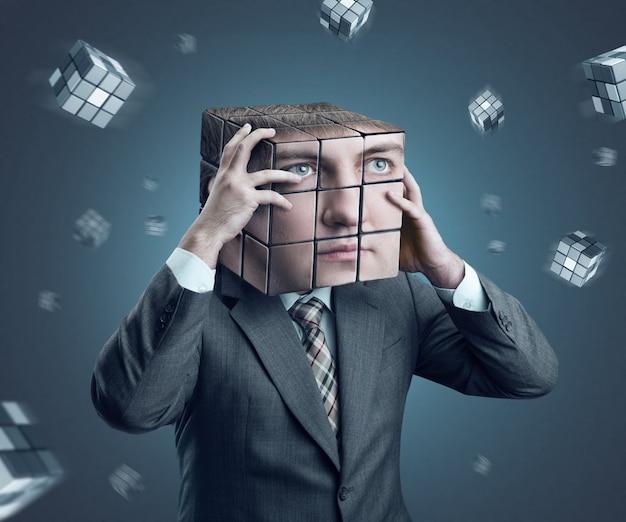 Businessman holding his rubik cube head