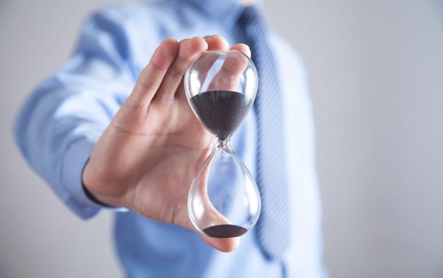 Businessman holding hourglass. deadline concept