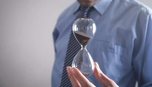 Businessman holding hourglass. deadline concept