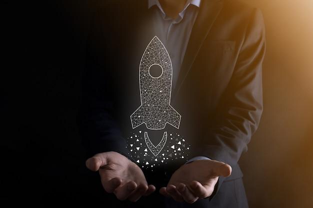 Бизнесмен, держащий значок прозрачной ракеты запускает