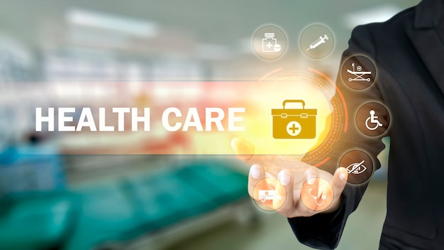 Businessman holding icons with medical symbols on blurry background
