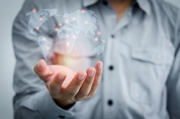Бизнесмен, держащийся в руке с глобальными сетями, общается