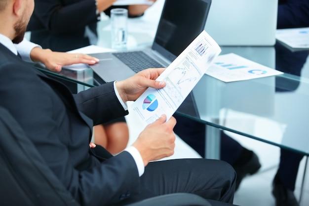 Бизнесмен держит в руках финансовый график
