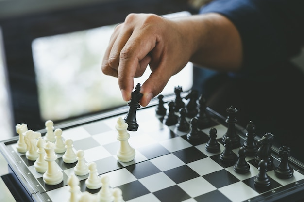 Businessman holding a king chess is placed on a chessboard.using