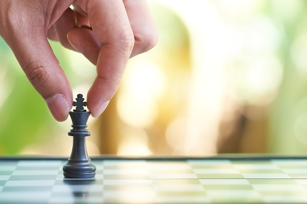 Businessman holding a king chess is placed on a chessboard