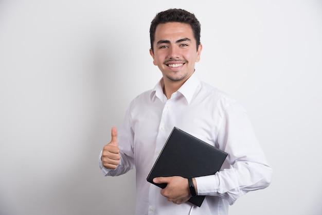 노트북을 들고와 흰색 바탕에 엄지 손가락을 보여주는 사업가.