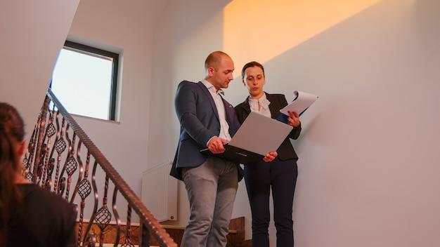 ビジネスビルの階段でオフィスの同僚と話しているラップトップを保持しているビジネスマン。現代の金融職場で働くプロの成功したビジネスマンのグループ。