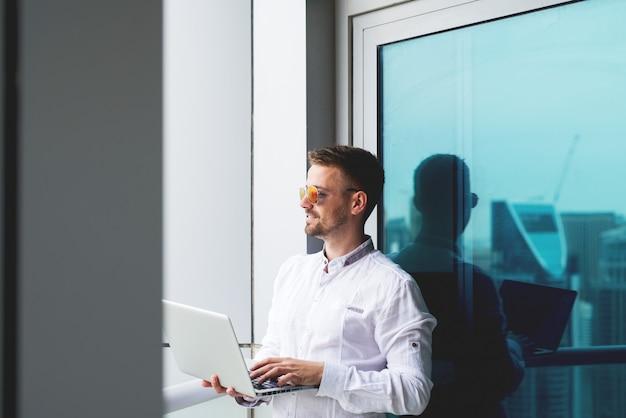 Businessman holding laptop office balcony working.