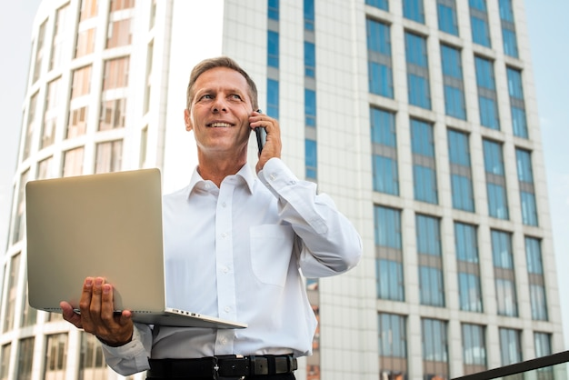 Businessman holding laptop talking on the phone