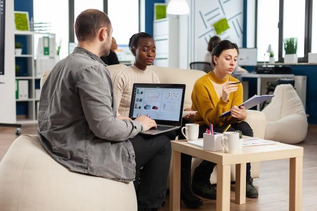 다양한 직원이 소파에 앉아 서류를 검토하는 프로젝트 계획을 설명하는 동안 금융 ghraphics와 노트북을 들고 사업가