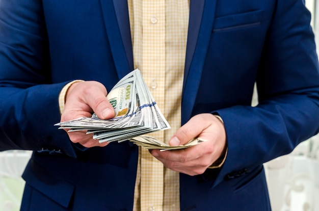 Businessman holding large amount of dollar and give you