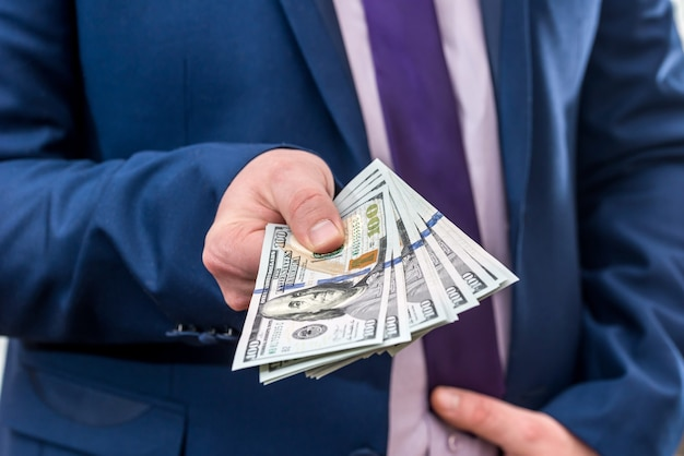 Бизнесмен держит большое количество долларов и дает вам