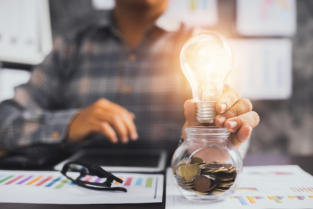 Бизнесмен держит лампочку на стакане монет
