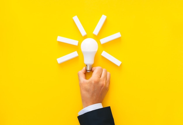 Businessman holding light bulb with wooden blocks with copy space. business start-up goals
