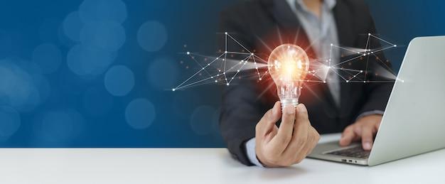 노트북을 사용하여 전구를 들고 사업가입니다. 창의적 혁신을 생각합니다. 전원 비전 및 아이디어 개념입니다.