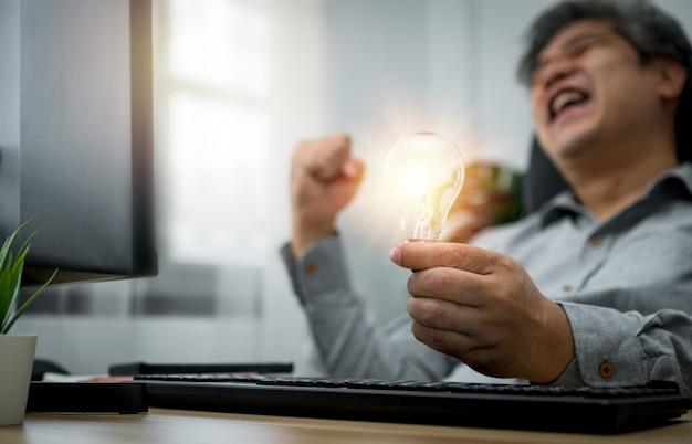 Бизнесмен держит лампочку и чувствует себя счастливым и взволнованным новыми идеями