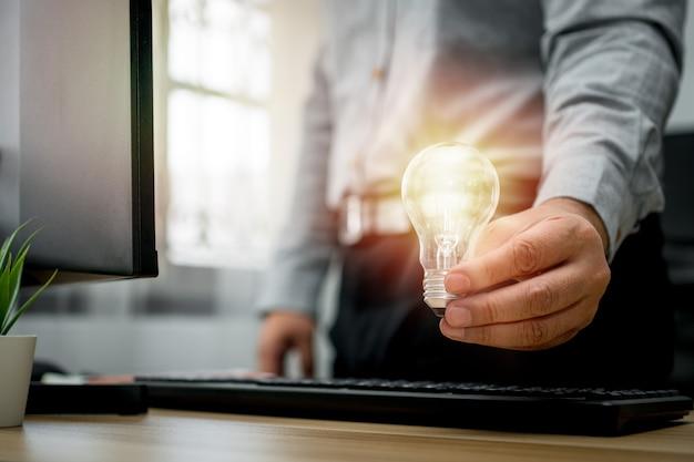 Бизнесмен держит лампочку и чувствует себя счастливым благодаря новым инновациям и идеям