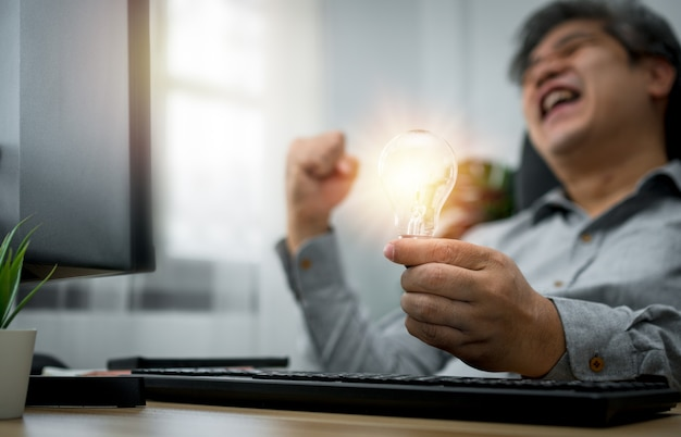 Businessman holding lightbulb and feeling delighted and excited by new ideas