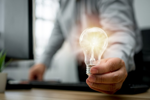 Businessman holding lightbulb and feeling happy by new innovation and ideas for success business panels.