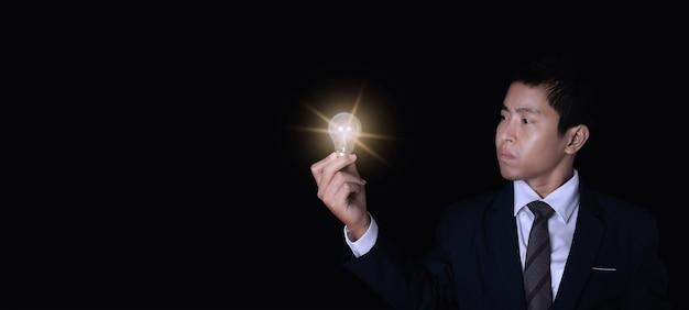 電球を保持しているビジネスマン。革新とインスピレーションのアイデアコンセプト