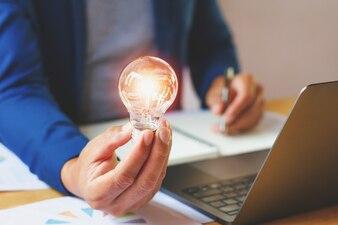 Businessman holding lightbulb in office
