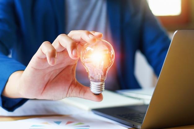 オフィスで電球を持つ実業家