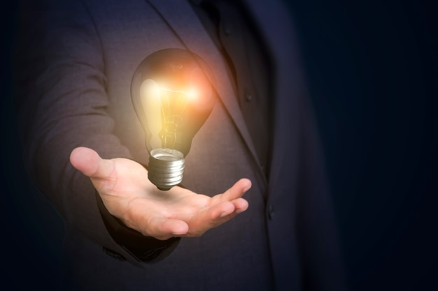 Businessman holding lightbulb of new ideas and creativity