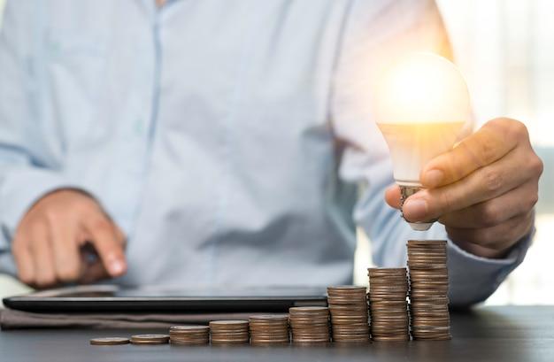 Бизнесмен держа лампочку которая накаляя на штабелированных монетках. идея творчества может заработать больше денег концепции.