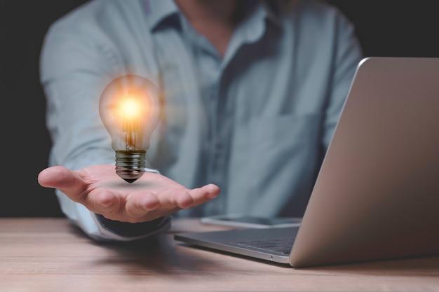 Бизнесмен, держащий лампочку, которая накаляется на деревянном столе с портативным компьютером как бизнес-решение и творческое понятие маркетинговой идеи.