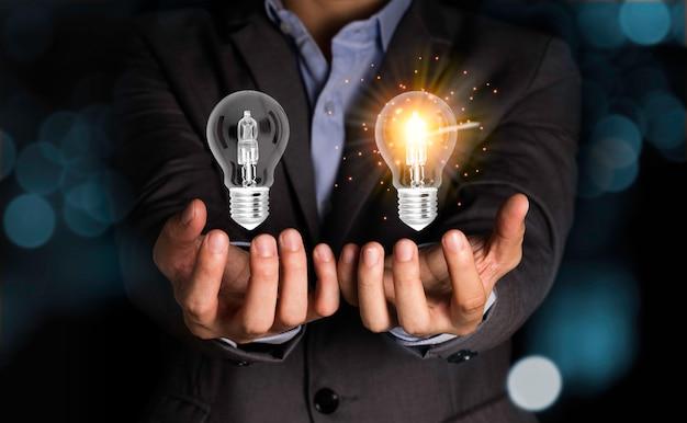Бизнесмен держа лампочки которые одна лампа накаляя и одна лампа чернят вне. концепция идеи творчества.