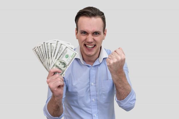 Бизнесмен держит много денег банкнот, изолированных на фоне серого цвета