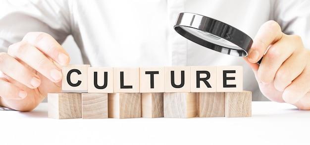 돋보기와 나무 블록을 들고 사업가입니다. 텍스트 문화와 나무 조각에 사업가 시계. 금융 시장. 융자