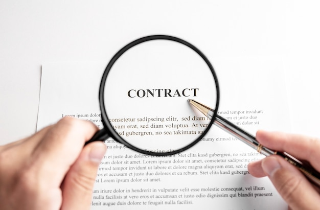 Businessman holding magnifying glass zoom and analyzing contract