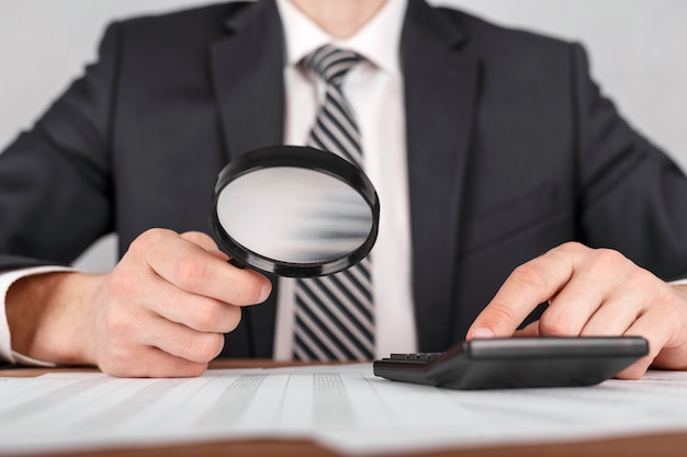 Businessman holding magnifying glass zoom and looking to documents