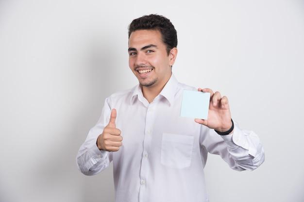 메모 패드를 들고와 흰색 바탕에 엄지 손가락을 보여주는 사업가.