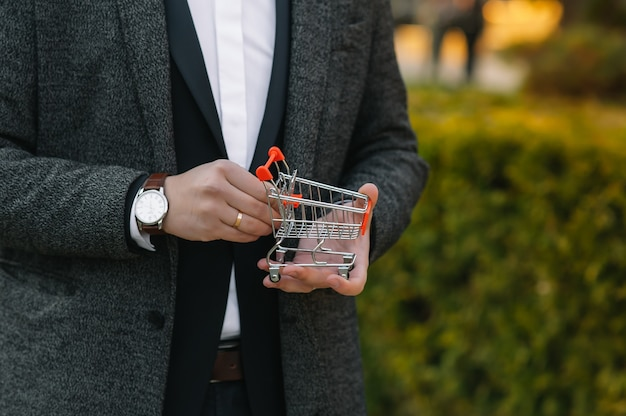 Businessman holding a miniature shopping cart