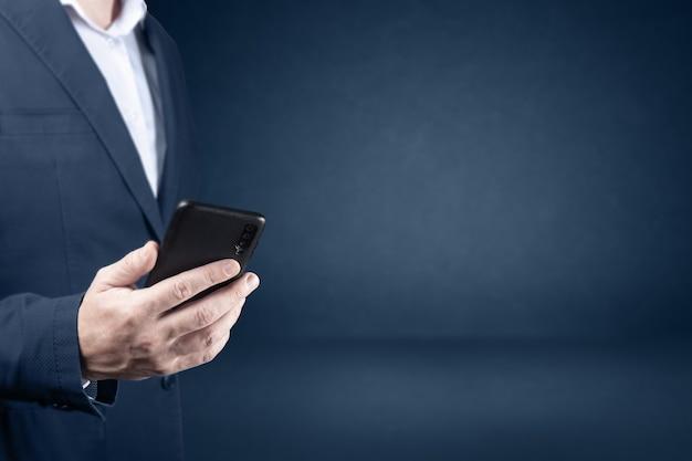 スーツを着た携帯電話の男を保持しているビジネスマンは電話を保持していますお問い合わせオンラインビジネス
