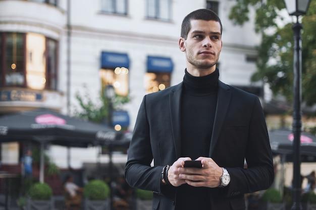 Бизнесмен, держа мобильный телефон и глядя на него на открытом воздухе