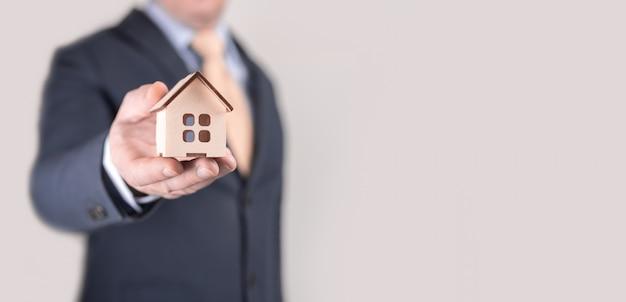 彼の手でモデル家を保持しているビジネスマン。手に家のモデルを持っている財産保険コンセプト保険代理店。住宅ローン保険の概念。コピースペース、バナー