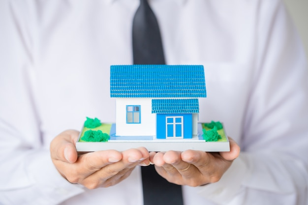 Businessman holding model house