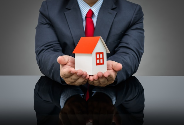 Businessman holding a model house