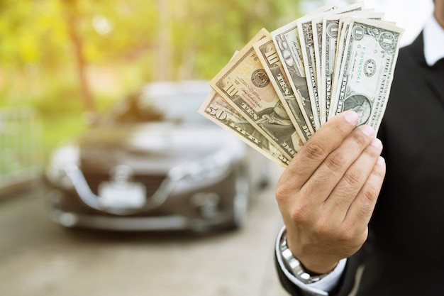 Businessman holding money in hand stand front car prepare pay by installments insurance, loan and buying car