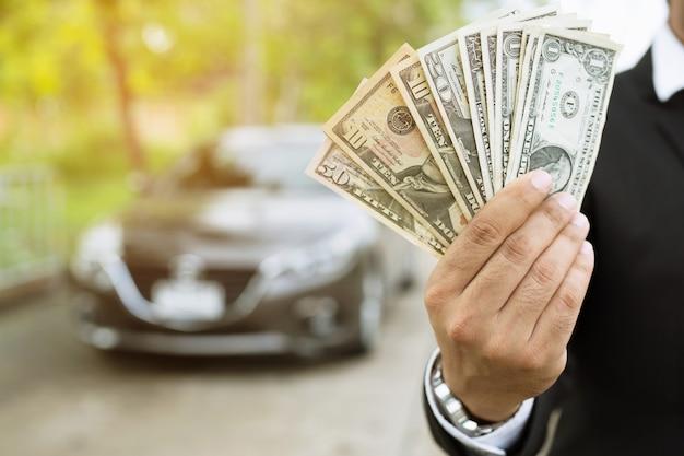 Бизнесмен, держащий деньги в руке, стоит перед автомобилем, готовит оплату в рассрочку, страхование, ссуду и покупку автомобиля