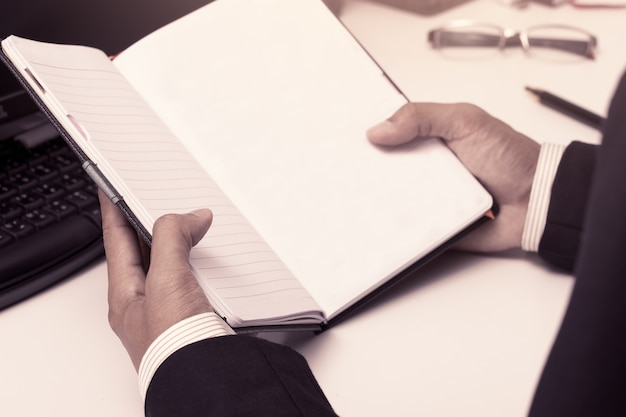 Businessman holding a notebook in office